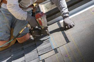 Person using a nail gun installing asphalt roof