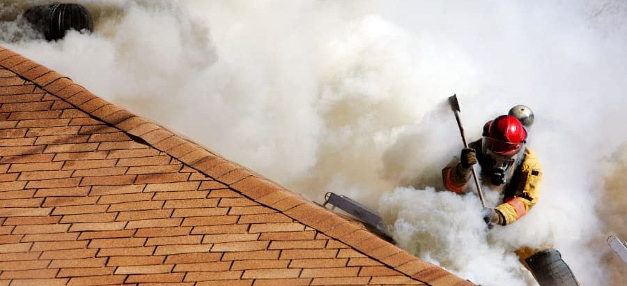 Firefighter on roof of building with smoke